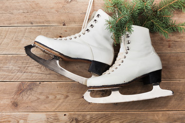 Vintage ice skates for figure skating with fir tree branch hanging on rustic background. Christmas decoration.
