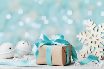 Christmas gift box and white jingle bell against blue bokeh background. Holiday greeting card.