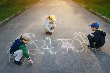 Children is drawing happy family on asphalt in spring park.