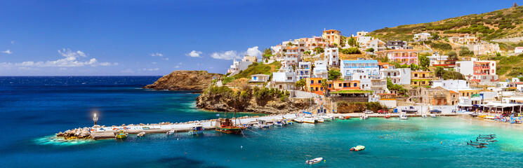 Crete, Greece. Harbor with marine vessels, boats and lighthouse. View from cliff on Bay with beach and architecture Bali - vacation destination resort with clear ocean water, Rethymno