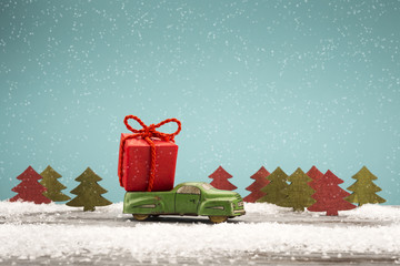 Toy car carrying a Christmas gift in a snowy landscape