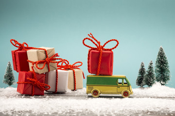 Toy truck carrying a Christmas gift in a snowy landscape
