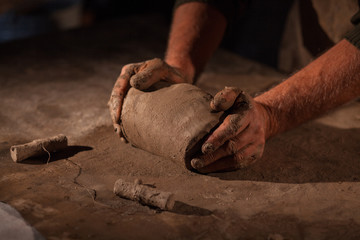 Hands of the potter knead clay.