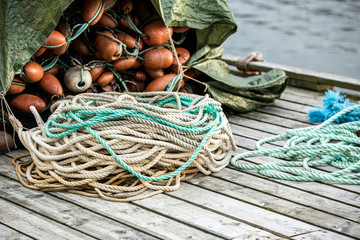 Many fishing nets and floats, stacked on a wooden dock. Fisheries, fishing. Fishing industry.  Background.