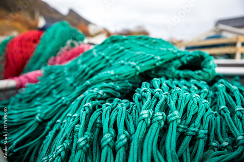 Many fishing nets and floats, stacked on a wooden dock  Fisheries