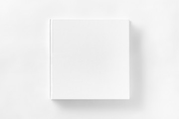 Mockup of closed blank square book at white textured paper  Wall mural