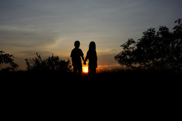 Front view of a full body of couple silhouettes holding hands and walking together looking each other in a date at sunset.