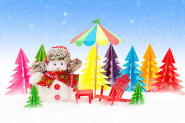 Christmas background, Snowman with sun lounger and beach umbrella.
