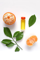 Serum with Vitamin C, tangerine and mandarin leaves isolated on white background