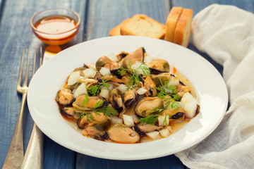 salad mussels with onion in sauce in white plate on wooden backg
