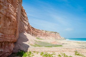 Towering red sandstone cliffs at Angola's coast line