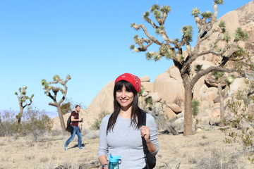 Hiker in front of Joshua Trees in Joshua Tree National Park, California.
