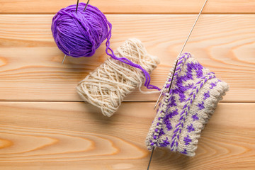 purple and white woolen yarn and knitted socks with a pattern on