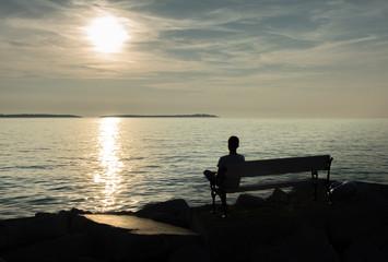 Einsamer Junge sitzt auf Bank an der Küste