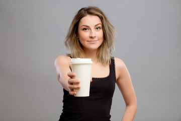 Young woman giving hot coffee to camera