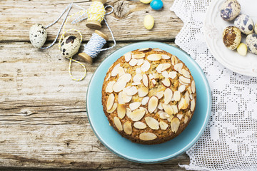 Simple homemade pecan pie decorated with petals of almond  a wooden background Serving Easter used blue and yellow colors, quail eggs, lavender flowers, vintage linen tablecloth handmade.