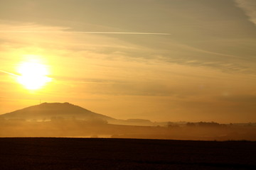Sun at sunrise on a misty morning with a hill in the background