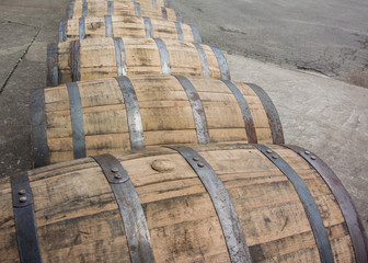 Bend in Row of Rolling Bourbon Barrels