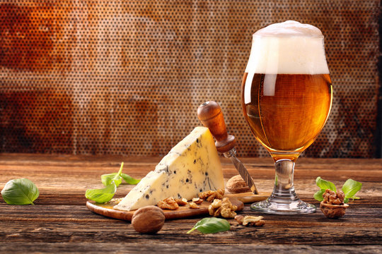 Blue cheese appetizer and beer on brown vintage background