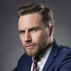 Portrait of young successful business man with beard and perfect hair style