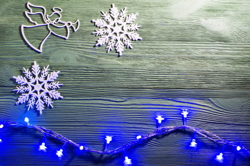 Christmas angel with wings and trumpet on cloud heralds the arrival of Christmas. Angel and snowflakes on wooden background, flat lay. Christmas background with garland lights