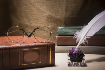 Vintage still life with glasses on old book near inkstand and feather on canvas background