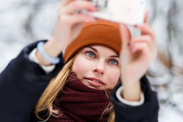 Blonde in hat making selfie
