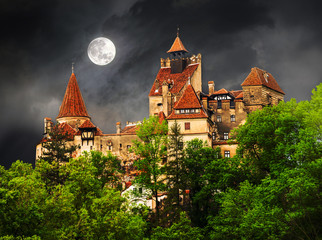 Beautiful and old architecture of the famous Dracula castle in Bran town, with the full moon on sky before the storm.
