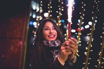 Beautiful young brunette woman enjoying Christmas or New Year night ona a city street. She holding sparklers and smiling.