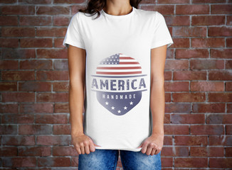 Woman in white t-shirt with text AMERICA HANDMADE on brick wall background. Manufacturing quality concept.