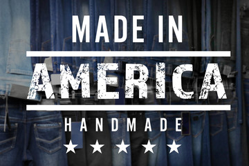 Text MADE IN AMERICA HANDMADE on jeans background. Manufacturing quality concept.