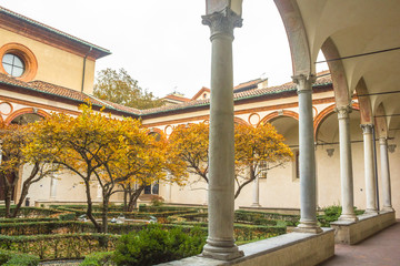courtyard of church Santa Maria Delle Grazie, access to it's refectory hosting The Last Supper painting by Leonardo da Vinci with trees in autumn colors.