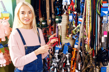 Pretty young woman selecting lead in pet shop