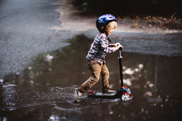 boy on scooter in puddle