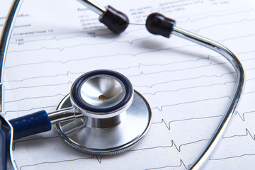Stethoscope on electrocardiogram lying at the desk