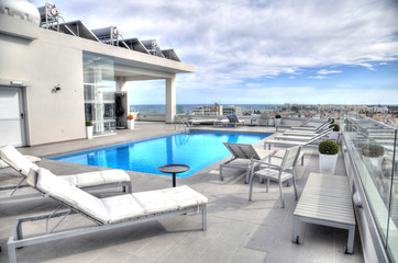 Luxury lifestyle concept in Larnaca, Cyprus: swimming pool in foreground, typical white architecture (top of roof deck building) in the background of Larnaca