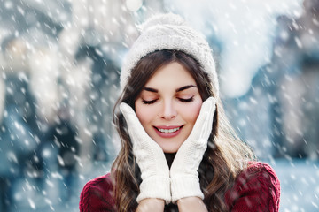 utdoor close up portrait of  young happy smiling girl walking on street. Model closed her eyes and touching face, wearing stylish winter hat and gloves. Magic snowfall. Christmas, New Year concept