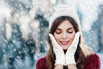 Outdoor close up photo of  young happy smiling girl walking on street. Model closed her eyes and touching face, wearing stylish winter hat and gloves. Christmas, New Year concept. Copy space for text