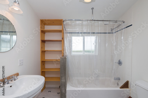 Bathroom With Wooden Cabinets And Round Mirror Bathtub Transparent Shower Curtain