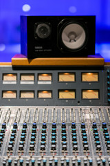 Vintage sound or audio mixer in a recording studio. Knobs, dials and sliders on a soundboard.