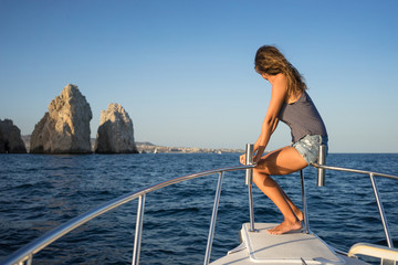 Young woman in the boat at sunset near the rock formations around the Arch in Cabo San Lucas, Mexico.
