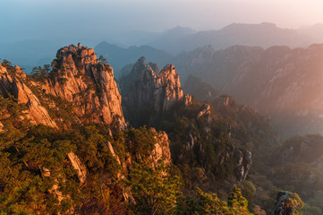 Sunrise from Lion Peak, Huangshan Mountain, China. Early morning sun lights the cliffs below and observation deck at Lion Peak, Yellow Mountains. Mountain range dissolves in the layers of atmosphere.