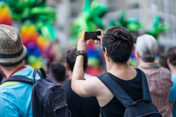 Man in the crowd celebrating Pride Parade. Taking a picture of the festivities with his mobile phone. During a march supporting marriage equality and LGBT rights.