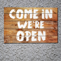Vintage Come in we are open wooden sign on gray stucco concrete wall.
