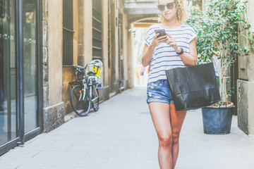 Summer sunny day.Girl with blond hair,dressed in striped t-shirt and denim shorts standing on street and using smartphone while holding black shopping bag.Young woman checking email on smartphone.