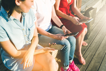 Close-up of smartphones and digital tablet in hands of three  young women sitting outdoors. Girls using digital gadgets. Girls  sitting on wooden steps.Floor made of wooden planks.