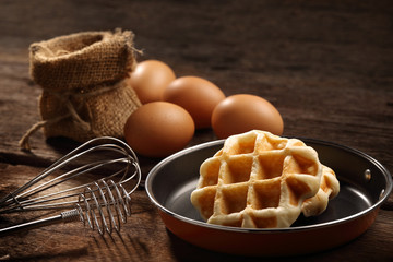 Close up baked waffles inside the teflon pan with hand mixer kitchen and eggs on wood background