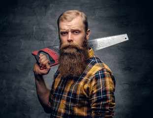 Bearded carpenter dressed in a plaid shirt holds handsaw.