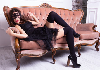 Sexy young woman lying on the sofa in black stockings and a mask. Sensual Woman in lace mask and stockings posing on vintage couch.