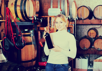 Woman having glass of wine in wine house